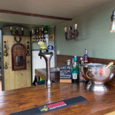 A view inside The Hoppy Mare mobile pub with beer pumps, drinks selection and signs